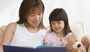 image of woman reading a book to a child